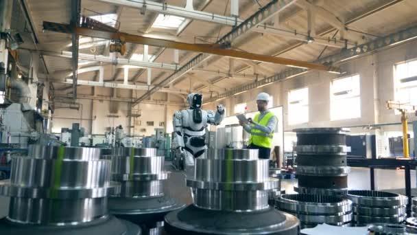 Průmyslová továrna s droidem, kterou spravuje muž