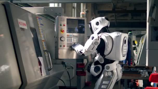 Fehér droid gombokat nyomogat egy gépen egy gyárban..