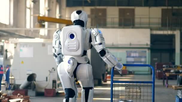Bionický robot si vytáhne vozík a chodí do továrny.