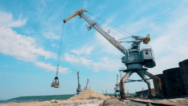 Kovový jeřáb přesunuje rozbité kameny a pracuje v docích.