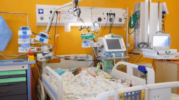 Child sleeps in a bed in a modern ward with medical equipment.