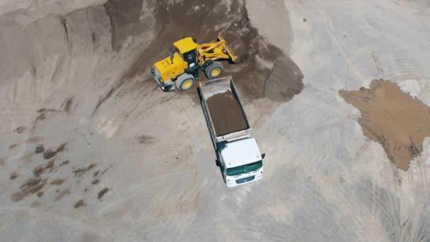 Žlutý traktor zavádí stroj s pískem v lomu. Zařízení těžebního průmyslu.