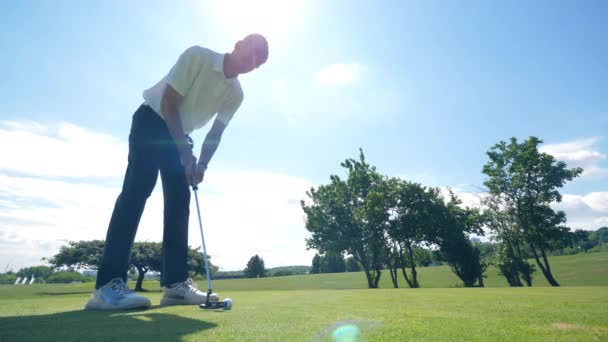 Jeden muž kope míč s klubem a hraje Golf.