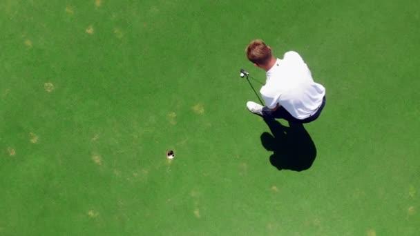 Golfer zasáhne míč do díry na golfingovním poli.