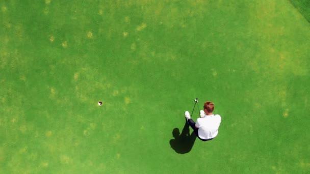 Profesionální golfista na kurzu, vložení koule do díry.