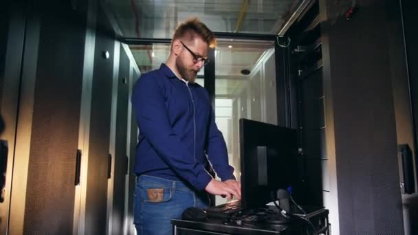 IT specialist, technician is operating a computer in a server unit