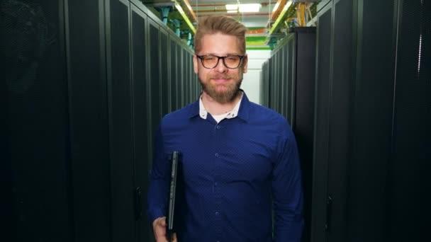 ein Mann mit Laptop steht in einem Serverraum und befestigt eine Brille