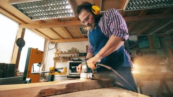Profesionální tesař používá brusnou maškarní a pracuje se dřevem v dílně.