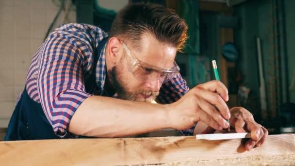 Osoba pracuje se dřevem, s tužkou a s pravítkem. Tesař pracuje.