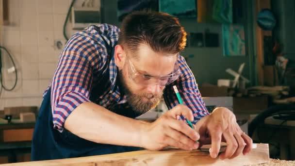 Dělník se vyznačuje tužkou. Tesař, řemeslník pracuje.