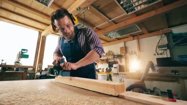 Při práci se dřevem se používá nástroj pro spojování mužů. Tesař pracuje.