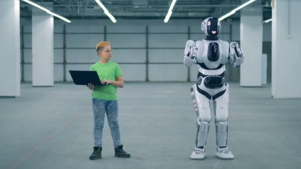 Kisfiú használ egy laptop-hoz irányít droid, közelről. Általános iskolai tanterv.
