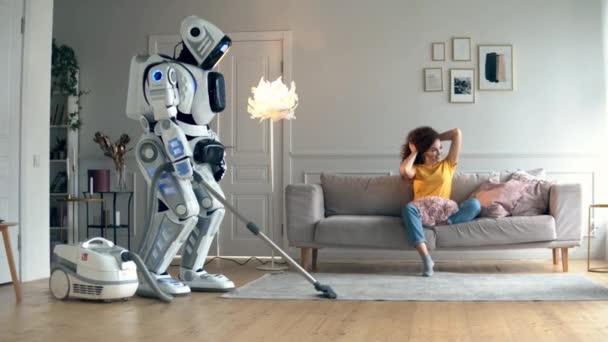 junge Frau beobachtet einen Roboter, der ein Zimmer saugt