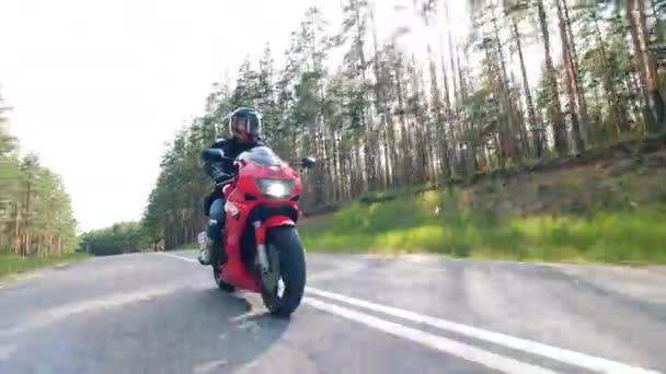 Motorcyklista závodí na jeho motorce. Asfaltová silnice s motorkářem, který řídí motocykl