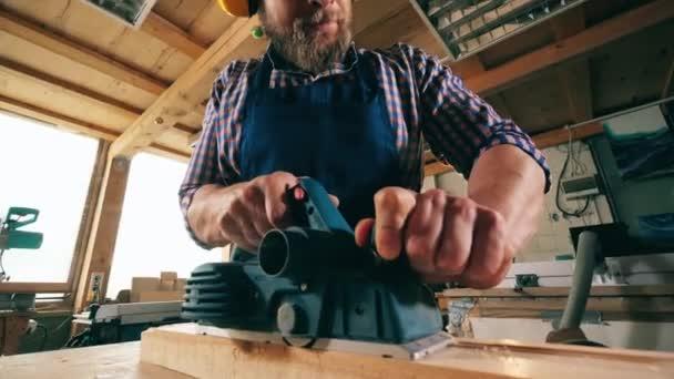 Mužský tesař piluje dřevo mechanicky. Tesař v truhlářské dílně