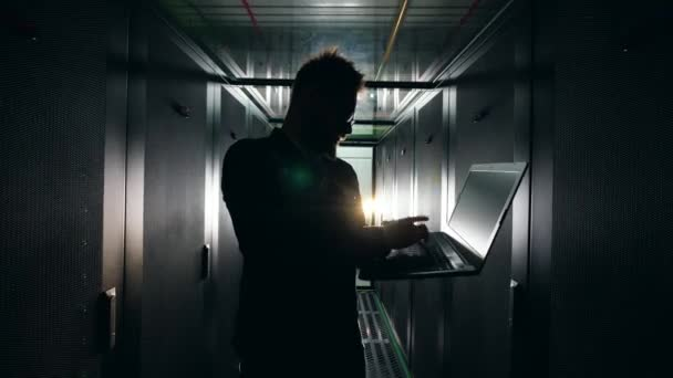 Silhouette of an IT worker with a laptop in the dark server unit. IT Engineer working in a server room.