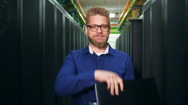 Počítačový inženýr stojí na serverové jednotce a usmívá se. Koncepce zabezpečení sítě.