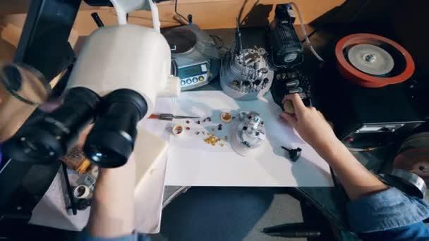 Juwelier benutzt Juwelierlupe bei Arbeit mit großem Ring.