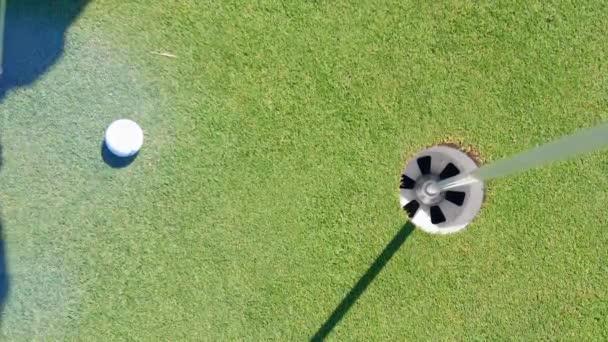 Weißer Ball kommt in ein Loch auf einem Golffeld.
