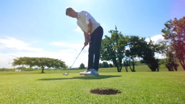 Golfer se pokouší dostat míč do díry na trávě. Golfový hráč na golfovém hřišti.