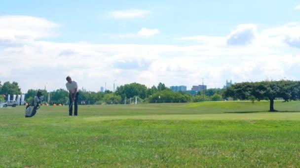 Člověk narazí na malý míček, zatímco hraje golf na hřišti. Golfový hráč na golfovém hřišti.