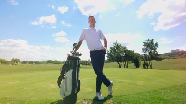 Na poli se svým vybavením stojí golfista.