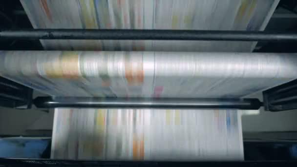 Noviny se přesunuté na válcovém dopravníku v typografii.