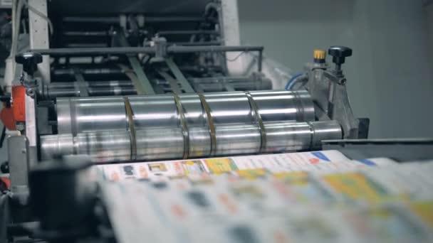 Mnoho novin se pohybuje po typografickém dopravníku s válečkem.