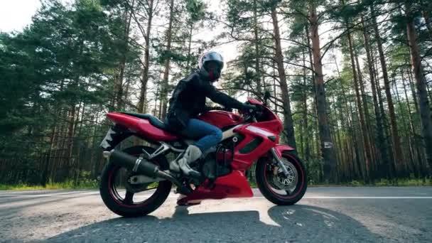 Motocyklista sedí na červeném kole na silnici.