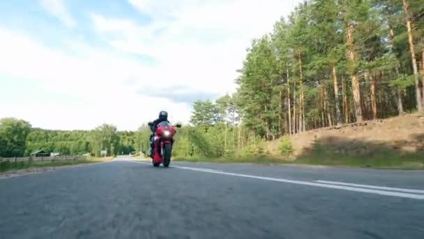 Biker v helmici jezdí po silnici na motorce.