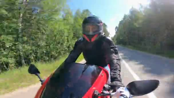 Motorcyclist driving fast on a road, wearing helmet.