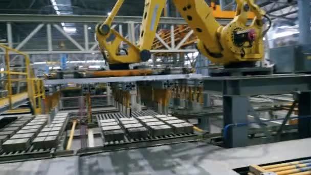 Robotické rameno přepravuje keramické výrobky v moderní průmyslové továrně.