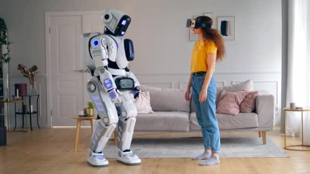 Ein menschenähnlicher Roboter berührt die Hand einer Dame mit Vr-Brille. Smart Home Konzept.