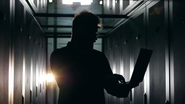 Silueta mužského technika pracuje v tmavém serverovém pokoji.