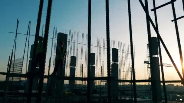 Sonnenuntergang-Baustelle: Bauarbeiter montieren Metallkarkasse