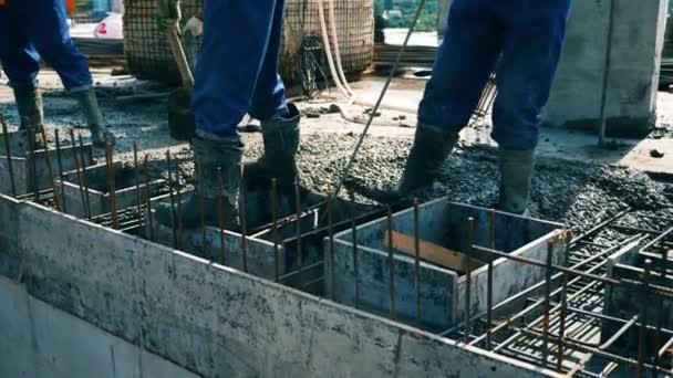 Építők szintű cement a padlón, miközben dolgozik egy építkezésen.