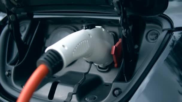 Moderní nabíječka připojená k elektrickému automobilu. Inovativní elektrická hybridní automobilovka.