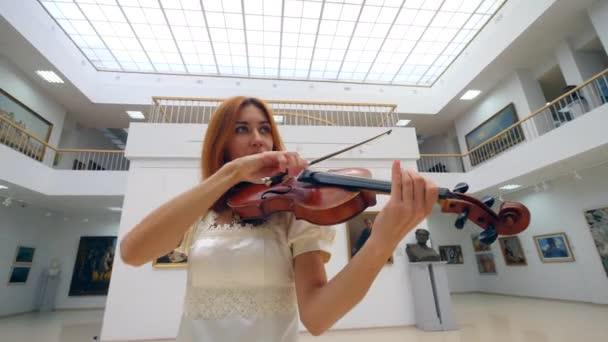 Hegedű kezd játszani egy női zenész, fehér ruhában