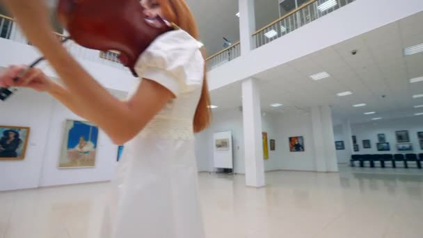 Gorgeous woman is playing the violin in a museum