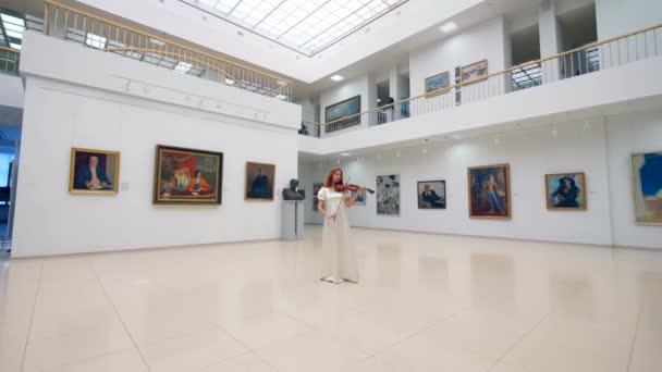 Lenyűgöző hölgy játszik a hegedű a galériában