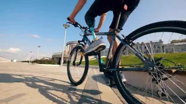 A bike is being ridden by a person with a prosthetic leg