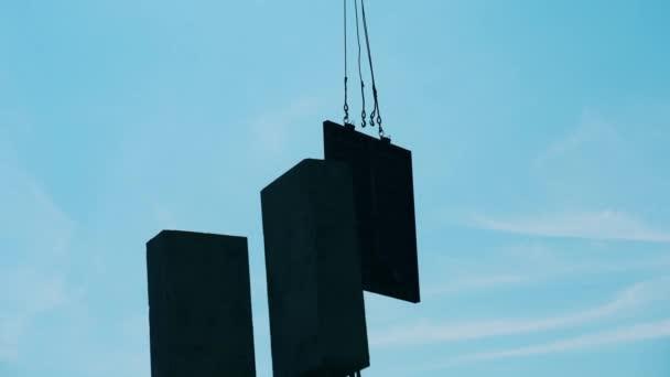 Jeřáb pohybuje kovovými bloky na staveništi.