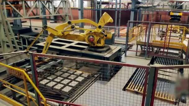 Robotické rameno přesouvá nově vyrobené výrobky do továrny