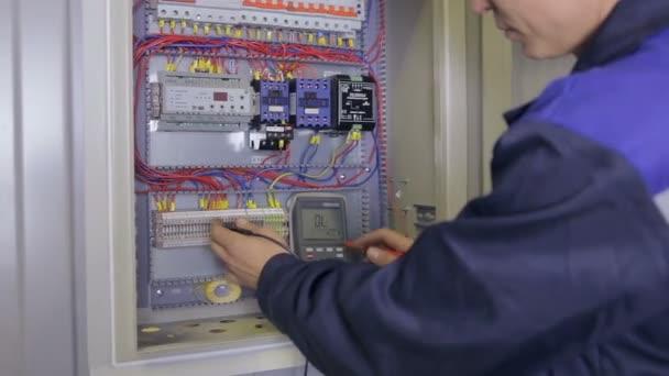 Elektrikář zkouší elektrickou energii. Průmyslový elektrikář testuje napětí pomocí multimetru na elektrickém štítu.