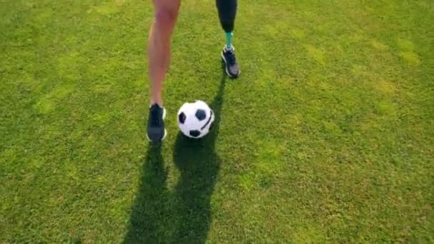 Green lawn with a physically challenged man playing soccer, football