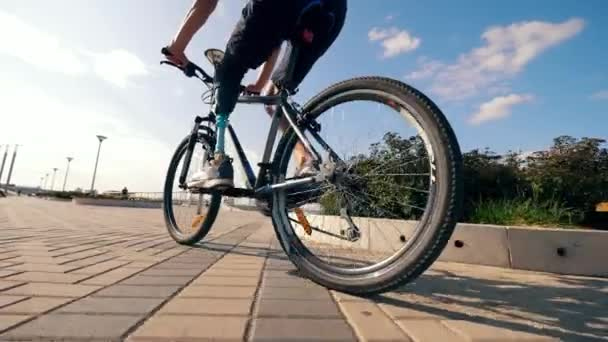 A man with a bionic leg is riding a bicycle outdoors