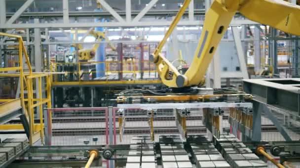 Automatizovaný robotický stroj přesouvá cihly z fungujícího dopravníku.