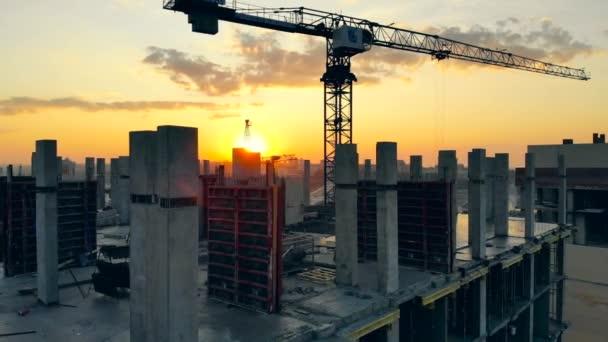 Vysoký jeřáb pracuje na staveništi s domem.