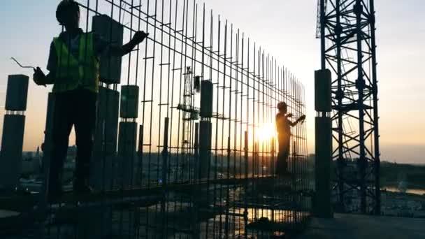 Sonnenuntergang Baustelle mit Ingenieuren, die ein Gerüst herstellen