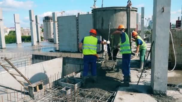A férfi munkások kipakolják a cementet a hordóból.